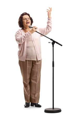 Full length portrait of an elderly female singing on a microphone isolated on white background