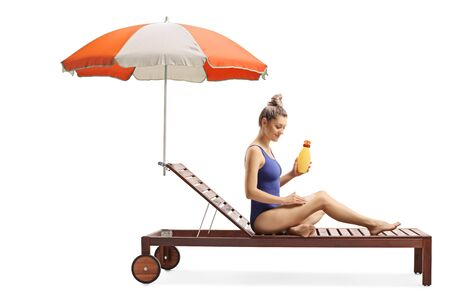 Full length shot of a young female applying a suncream and stting on a sunbed with umbrella isolated on white background