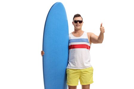 Young guy holding a surfboard and making a thumb up gesture isolated on white background Stock Photo