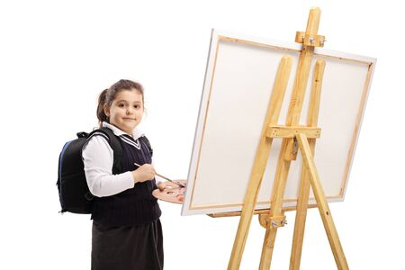 Schoolgirl painting on a canvas and looking at the camera isolated on white background