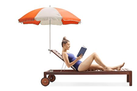 Full length shot of a young woman reading a book and relaxing on a sunbed under umbrella isolated on white background