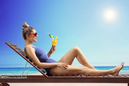 Full length shot of a young woman sunbathing on a beach with a cocktail