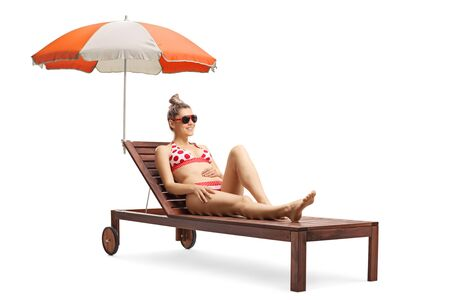 Full length shot of a young beautiful woman in bikini on a sunbed with umbrella isolated on white background Stockfoto