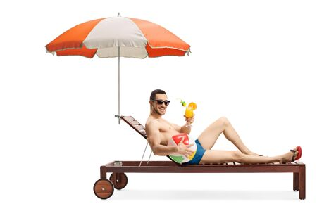 Full length shot of a young man on a sunbed with an umbrella holding an inflatable ball and a cocktail isolated on white background