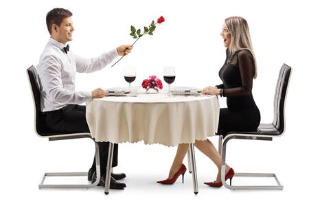 Full length profile shot of a young man giving a red rose to a young woman at a restaurant table isolated on white background