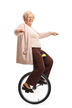 Full length shot of a cheerful senior woman riding a unicycle and balancing with hands isolated on white background 스톡 콘텐츠