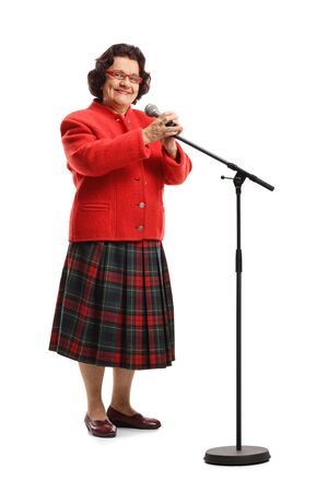 Full length portrait of an elderly female singer with a microphone smiling at the camera isolated on white background