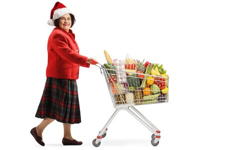 Full length shot of a senior woman with santa hat shopping food for chistmas holidays with a shopping cart isolated on white background