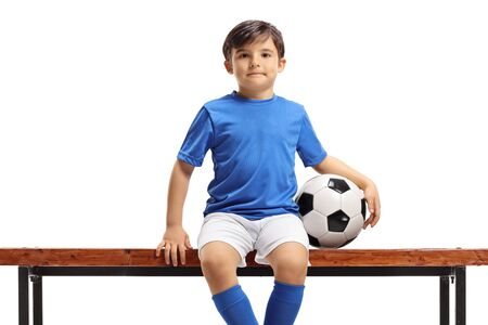 Boy with football sitting on a bench isolated on white background Stockfoto