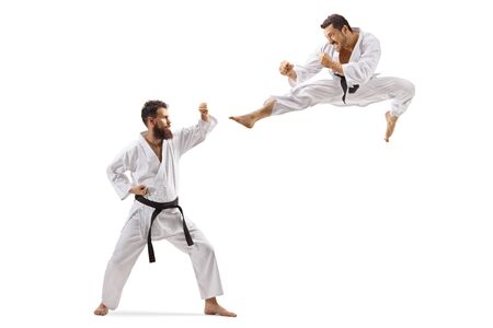 Disparo de longitud completa de dos hombres en kimono peleando aislado sobre fondo blanco.