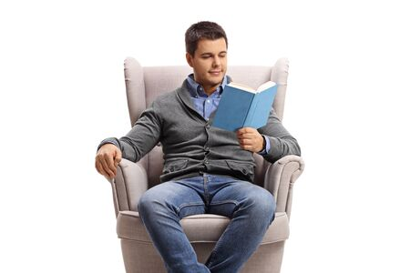 Young man in an armchair reading a book isolated on white background