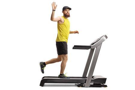 Pełne ujęcie młodego brodatego mężczyzny biegnącego na bieżni i machającego do kamery na białym tle Zdjęcie Seryjne
