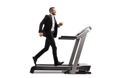 Aufnahme in voller Länge von einem jungen Mann in einem Anzug, der auf einem Laufband läuft, isoliert auf weißem Hintergrund