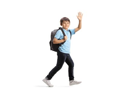 Full length shot of a schoolboy with a backpack running and waving at the camera isolated on white background 写真素材