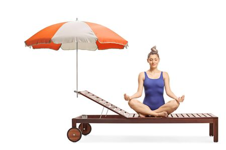 Young woman in a swimming suit meditating on a sunbed under umbrella isolated on white background
