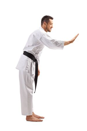Full length profile shot of a man in karate kimono gesturing with hand isolated on white background 写真素材
