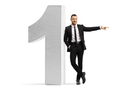 Full length portrait of a young businessman leaning on a large number one and pointing to the side isolated on white background