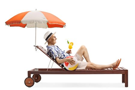Full length profile shot of a senior man on a sunbed with a ball and a cocktail isolated on white background