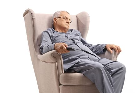 Elderly man in pyjamas sleeping in an armchair and holding a remote control isolated on white background 写真素材