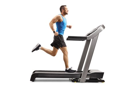 Full length shot of a muscular man running on a treadmill isolated on white background 写真素材