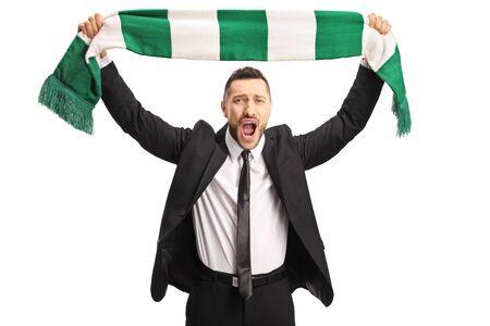 Jeune homme gai dans un costume acclamant avec une écharpe d'isolement sur le fond blanc