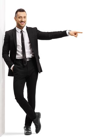 Full length portrait of a businessman leaning on a wall and pointing to the side isolated on white background 写真素材