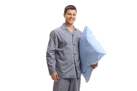 Young man in pajamas holding a pillow and smiling isolated on white background 写真素材