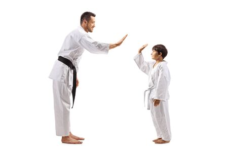 Full length profile shot of a boy and man in karate kimonos gesturing high-five isolated on white background