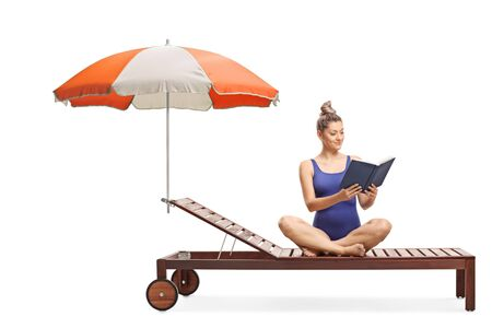 Young woman in a swimming suit sitting on a sunbed with umbrella and reading a book isolated on white background