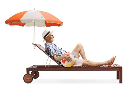 Full length shot of an elderly man enjoying on a sunbed under umbrella with an inflatable beach ball isolated on white background