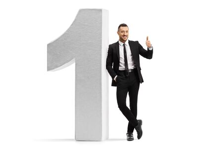 Full length portrait of a young man in a black suit and tie leaning on number one and showing thumbs up isolated on white background
