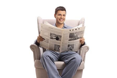 Young man in pajamas seated in an armchair with a newspaper  isolated on white background