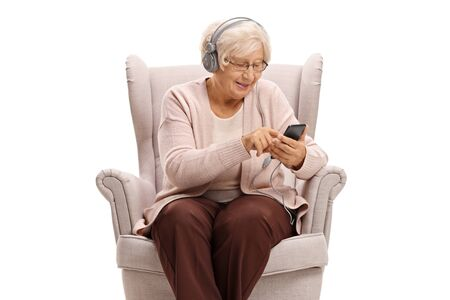 Senior woman sitting in an armchair and listening to music on a phone isolated on white background