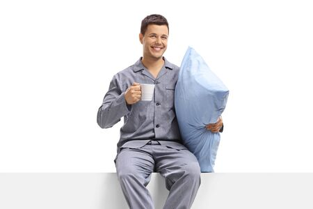Man in pajamas holding a cup and a pillow and sitting on a panel isolated on white background