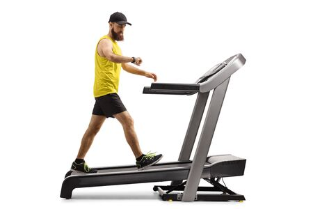 Full length profile shot of a bearded guy walking on a treadmill and looking at his smartwatch isolated on white background