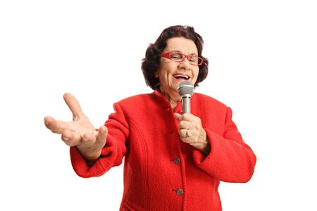 Cheerful elderly lady singing on a microphone and enjoying isolated on white background