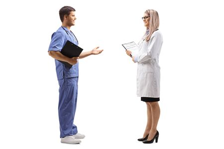 Full length profile shot of female and male doctor having a conversation isolated on white background 写真素材
