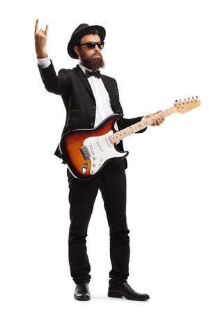 Full length portrait of a male musician with an electric guitar making a peace sign isolated on white background 写真素材