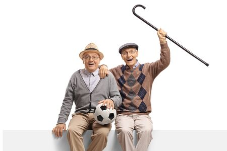 Two senior men with a football seated on a panel isolated on white background 写真素材