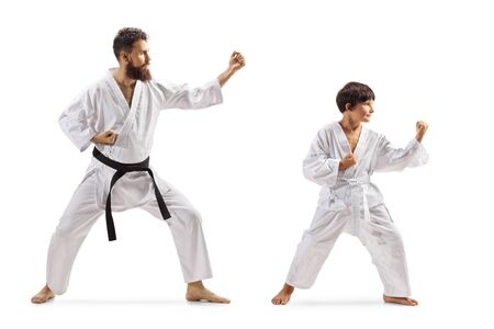 Full length shot of a boy and man in kimonos practicing karate isolated on white background 写真素材