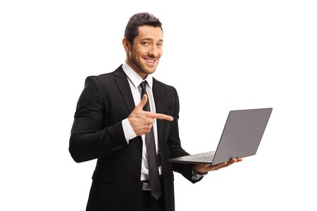 Young professional man in a suit holding a laptop and pointing at it isolated on white background
