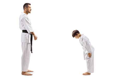 Full length shot of a boy in karate kimono bowing to instructor isolated on white
