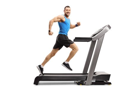 Full length shot of a young man in sportswear running on a treadmill and looking at the camera isolated on white