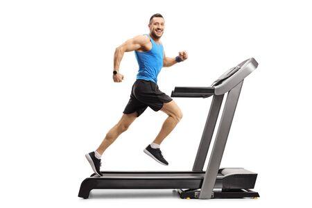 Photo de toute la longueur d'un jeune homme en vêtements de sport courant sur un tapis roulant et regardant la caméra isolée sur blanc