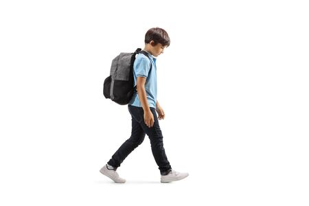 Full length profile shot of a sad schoolboy walking with his hand down isolated on white Stock Photo