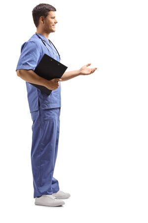 Full length profile shot of a medical person in a blue uniform holding a clipboard and gesturing with hand isolated on white Stock Photo