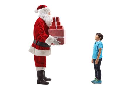 Full length shot of Santa Claus giving a pile of presents to a boy isolated on white
