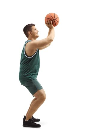 Full length profile shot of a man in a sports jersey shooting with a basketball isolated on white