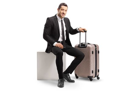 Full length shot of a businessman with a suitcase sitting on a white cube and looking at the camera isolated on white background