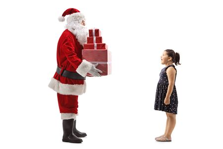 Full length shot of Santa Claus giving Christmas presents to an excited girl isolated on white background 写真素材